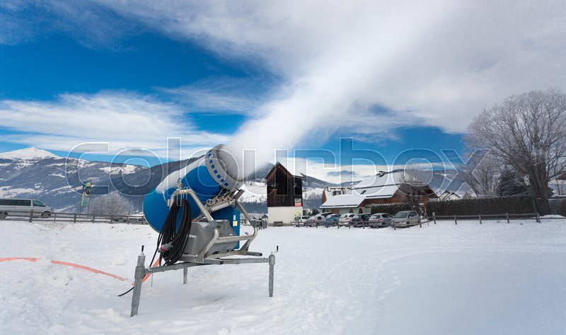 Making artificial snow on ski resort at cold day in Alps, stock photo
