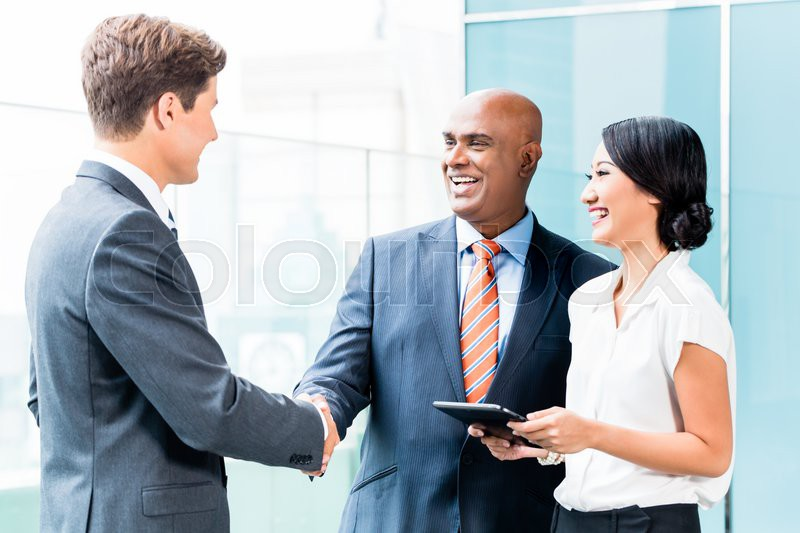 Indian CEO and Caucasian executive having business handshake in front of city skyline, stock photo