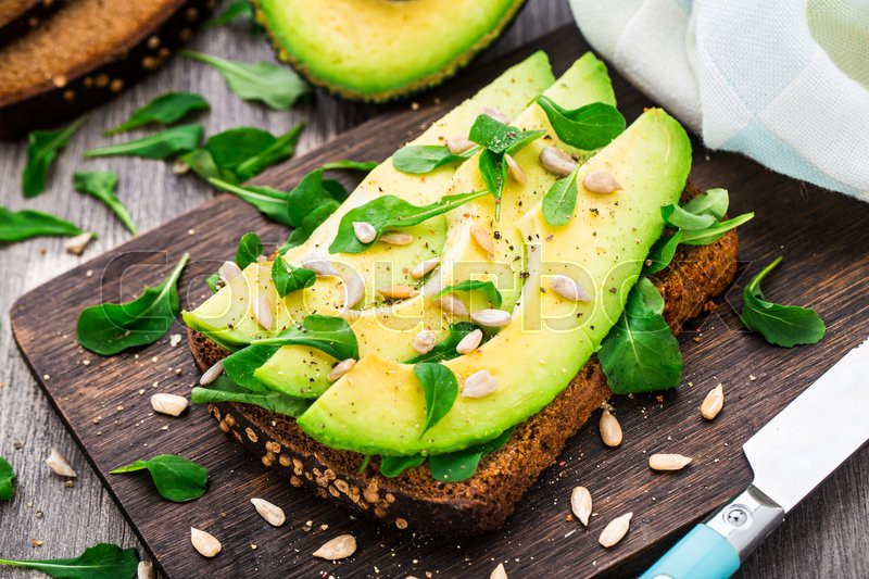 Stock image of 'Avocado sandwich with arugula and sunflower seeds'