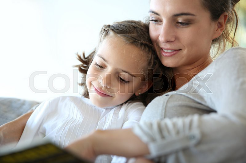 Mom with little girl reading book in sofa, stock photo