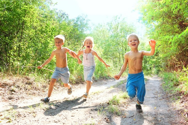 Stock image of 'Group of 5-6 year old happy kids running in the woods'