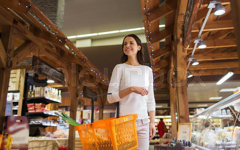 Sale, shopping, consumerism and people concept - happy young woman with food basket in market, stock photo