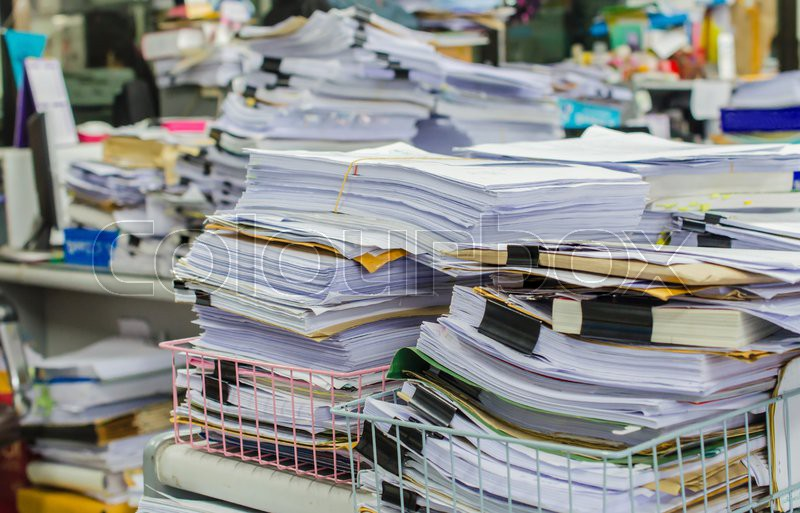 Pile of documents on desk stack up high waiting to be managed, stock photo