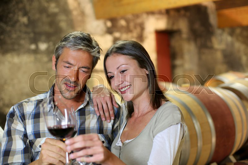 Couple of winemakers tasting red wine, stock photo