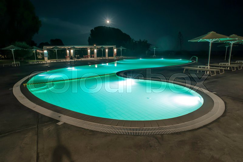 Pool, sunbeds and umbrellas at night. Night lights. Greece, Gythio, stock photo