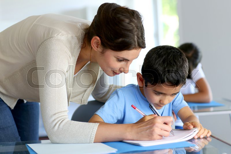Teacher helping young boy with writing lesson, stock photo