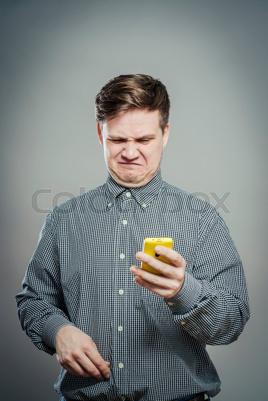 A confused young man looking at mobile phone, stock photo