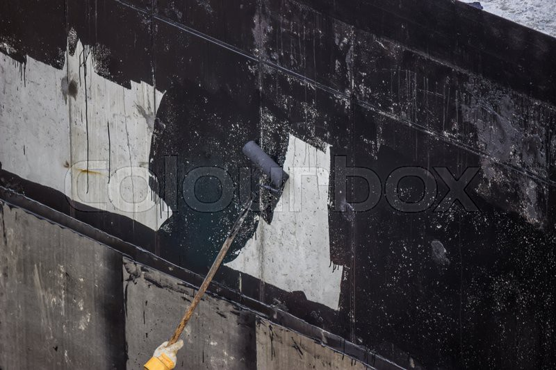 Waterproofing worker painting exterior concrete wall with tar insulation material at for Exterior concrete wall insulation
