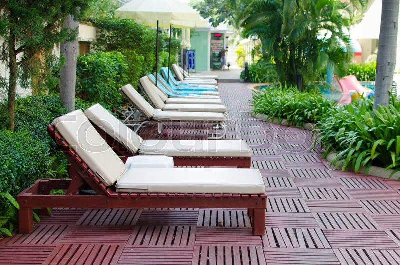Stock image of 'Beach chairs near swimming pool in tropical resort.'