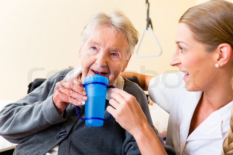 Nurse In Nursing Home Giving Drink To Elderly Woman