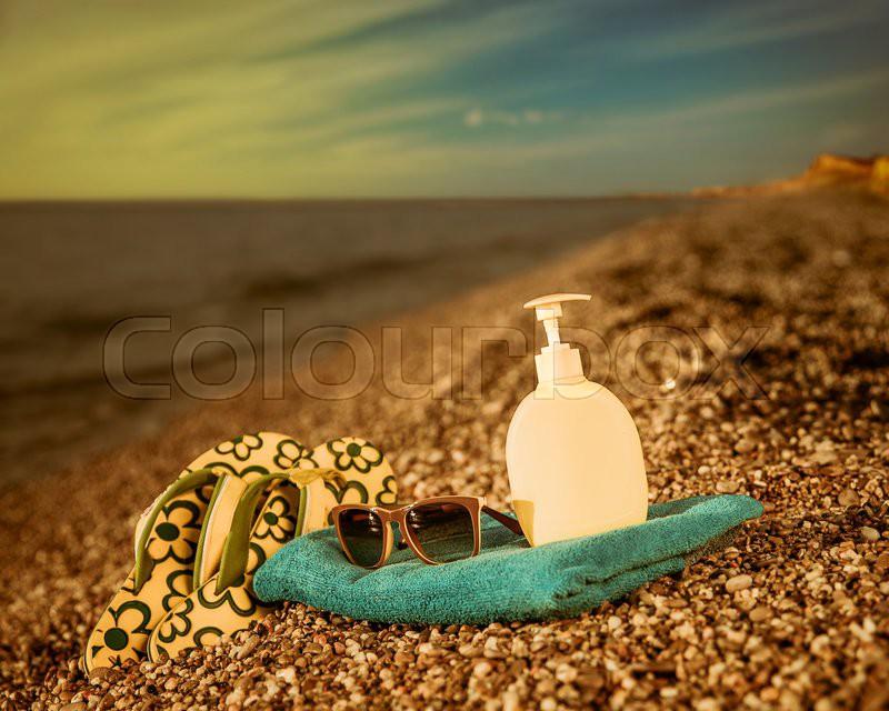 Spanking, cream and towel on the beach, stock photo