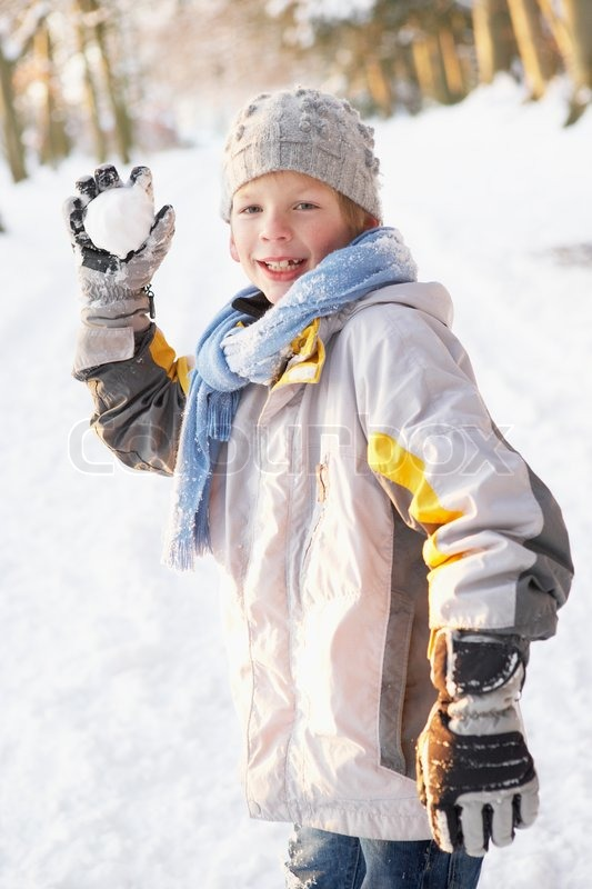 boy about to throw snowball in snowy woodland