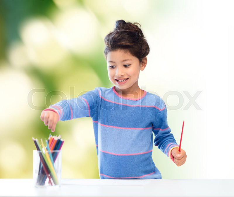 Children, creativity and happy people concept - happy little girl drawing with coloring pencils over green background, stock photo