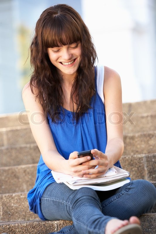 Teenage Student Sitting Outside On College Steps Using Mobile ...