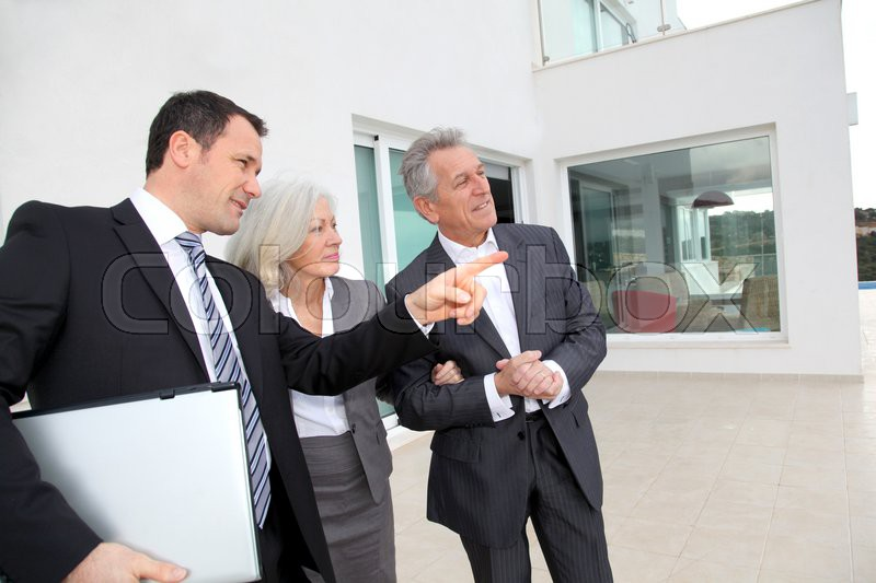 Senior couple visiting luxury villa with real-estate agent, stock photo