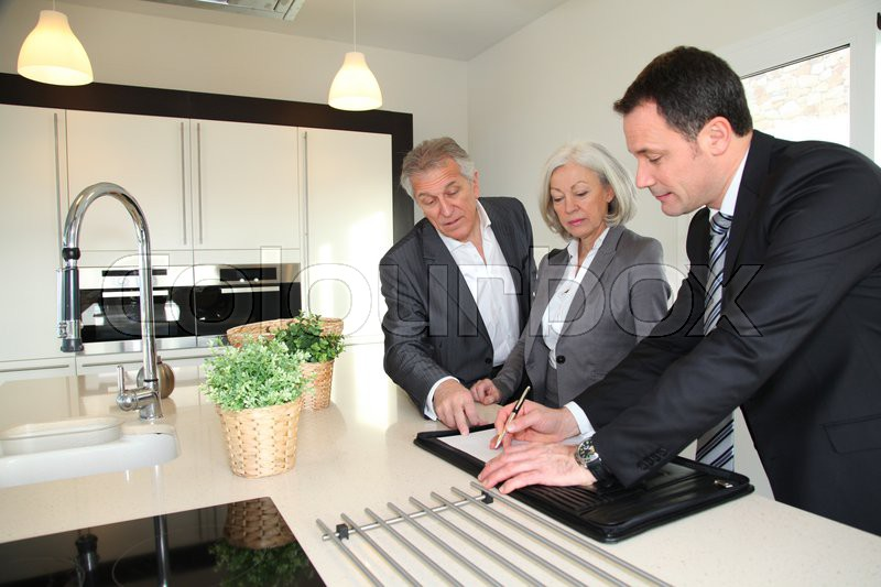 Real-estate agent showing interior of house to senior couple, stock photo