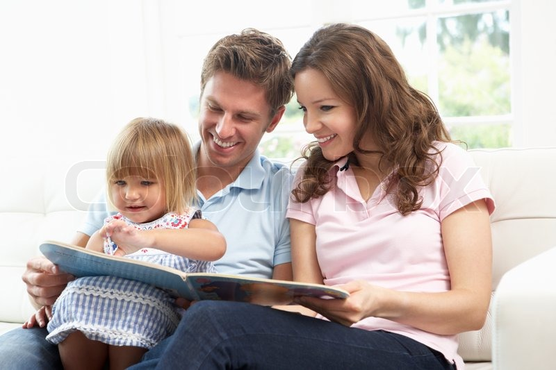 Family Sitting On Sofa Reading Book At Home, stock photo