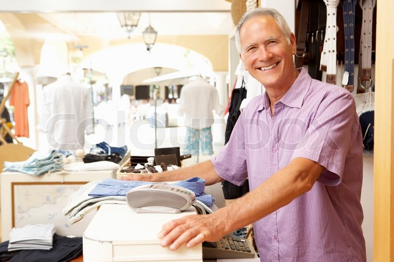 male sales assistant at checkout of clothing store   stock photo    male sales assistant at checkout of clothing store  stock photo