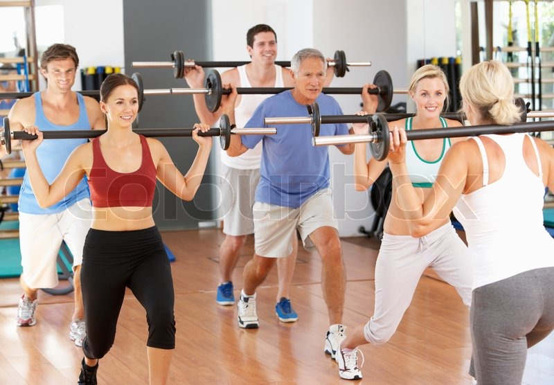 group of people lifting weights in gym stock photo