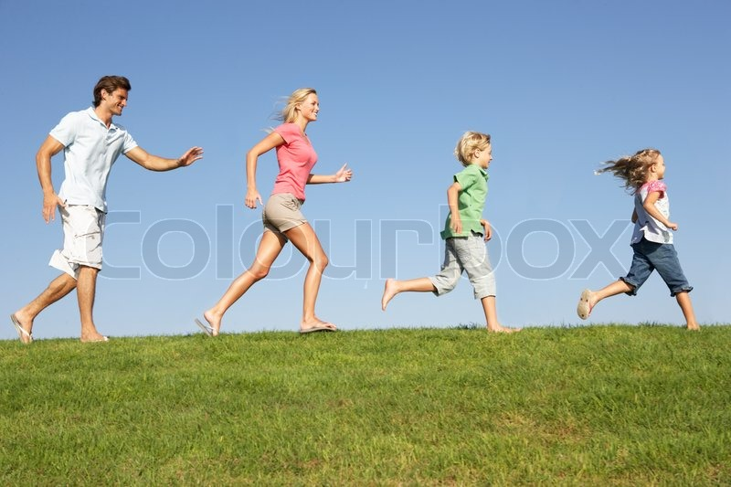 Image of young family parents with children running through field