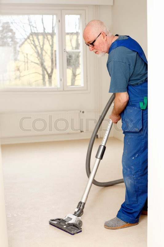 vacuum cleaning senior worker in overall during apartment
