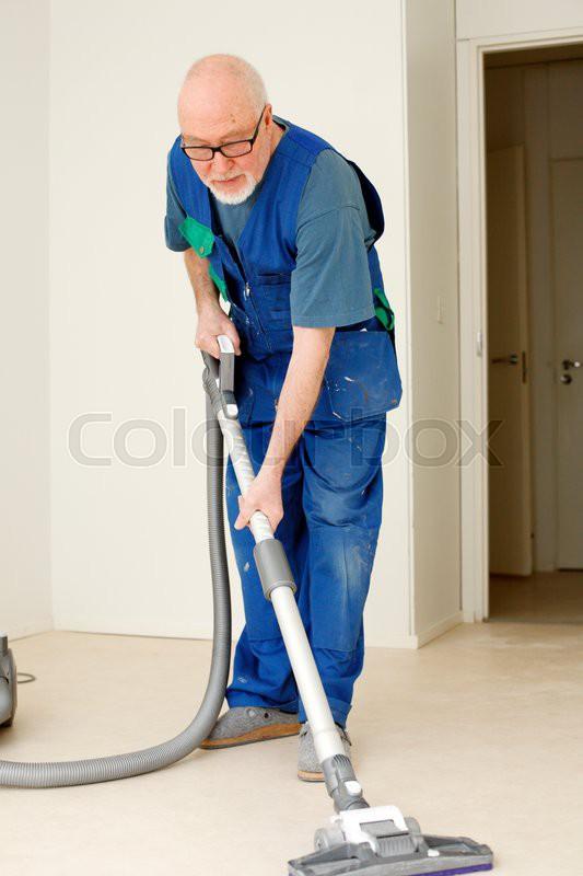 elder craftsman vacuum cleaning floor in apartment during