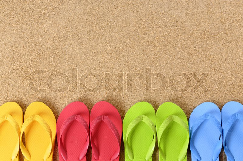 Flip flops in a row on a sandy beach. Space for copy, stock photo