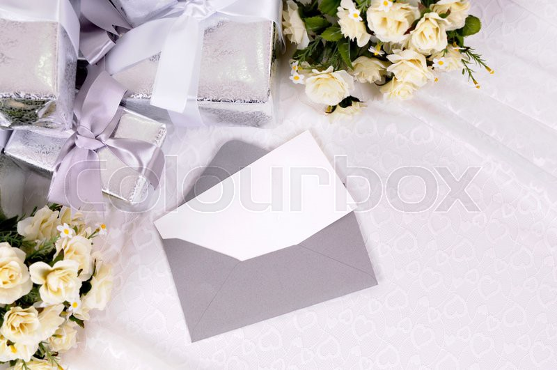 Blank invitation or thank you card with several wedding gifts and white rose bouquet laid on bridal lace. Space for copy, stock photo
