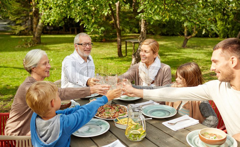 Family, generation, home, holidays and people concept - happy family having dinner and clinking glasses in summer garden, stock photo