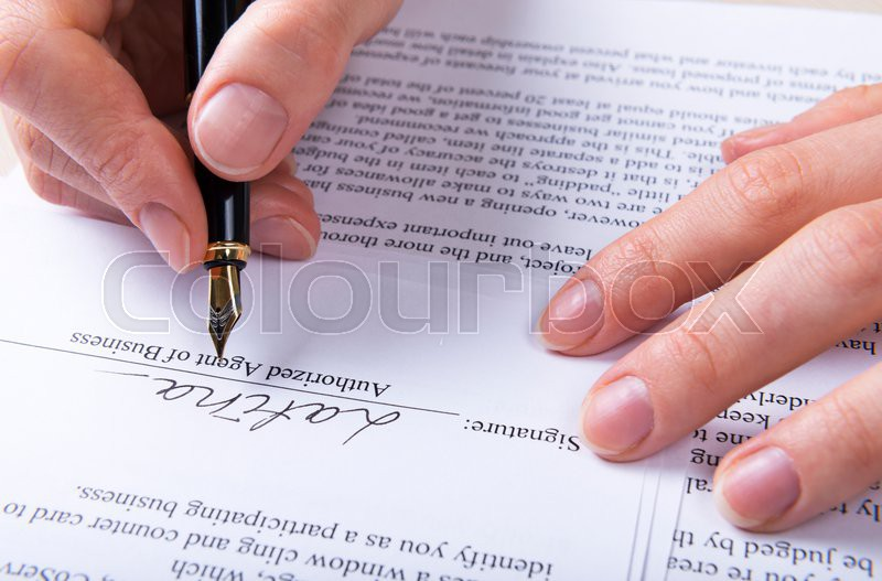 Hand puts the signature in the contract, stock photo