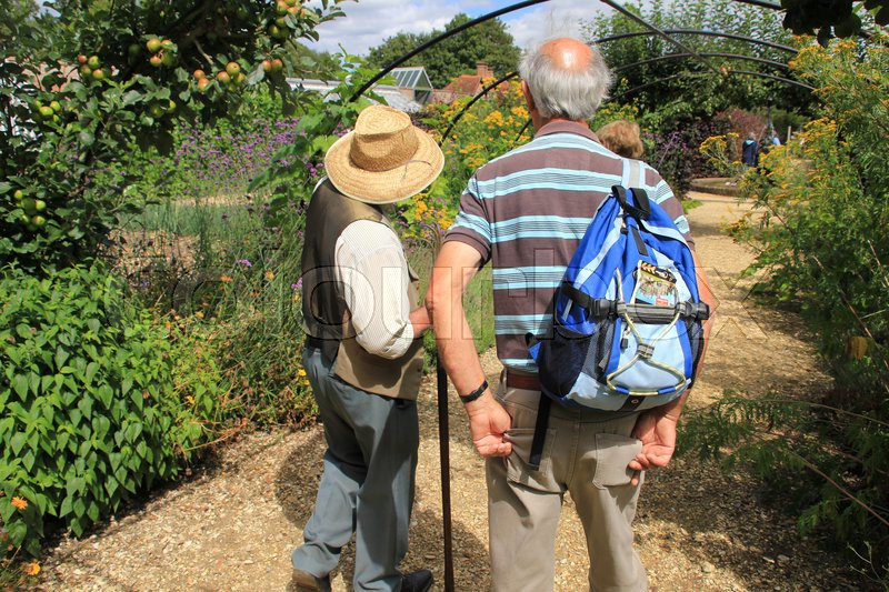The gardener tells the tourist a story about the wonderful garden in the summer in England, stock photo