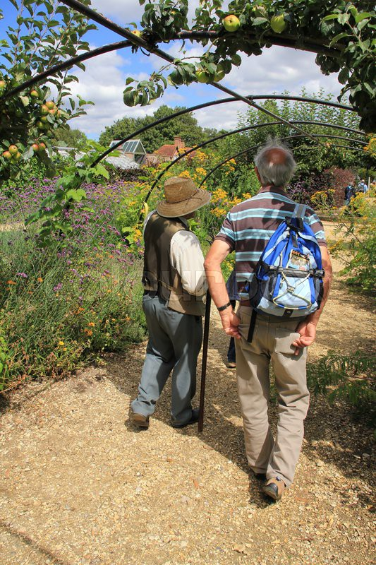 The gardener shows the tourist the way in the wonderful garden in the summer in England, stock photo