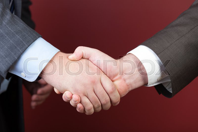 Business negotiations illustrated with a close up of a handshake between two men, stock photo