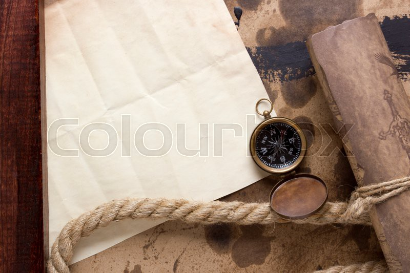 Roll of parchment with a compass and marine rope, stock photo