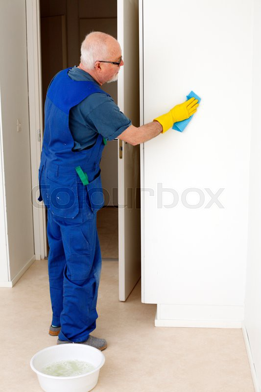 Senior painter cleaning dust from wall before painting it, stock photo