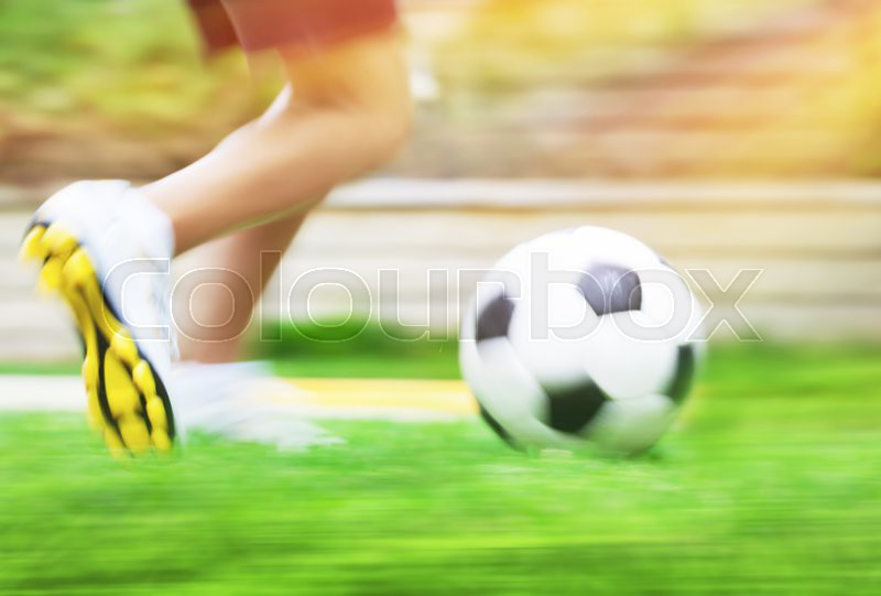 Football game slow motion, body part, sportive teen boy runs for ball, soccerl championship, active teens lifestyle, recreation and hobby, stock photo