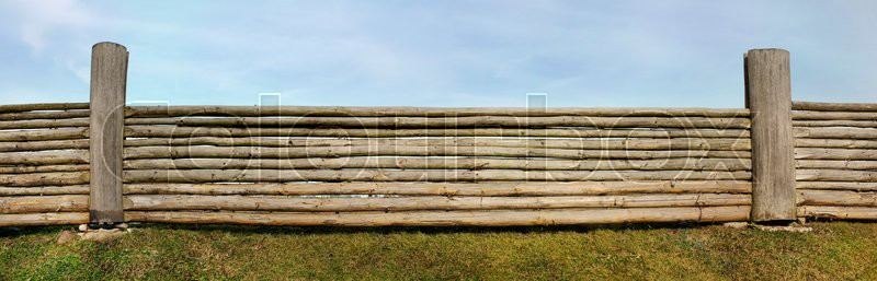 The panoramic image of very long rural fence against the sky made of the pared-down pine trunks, stock photo