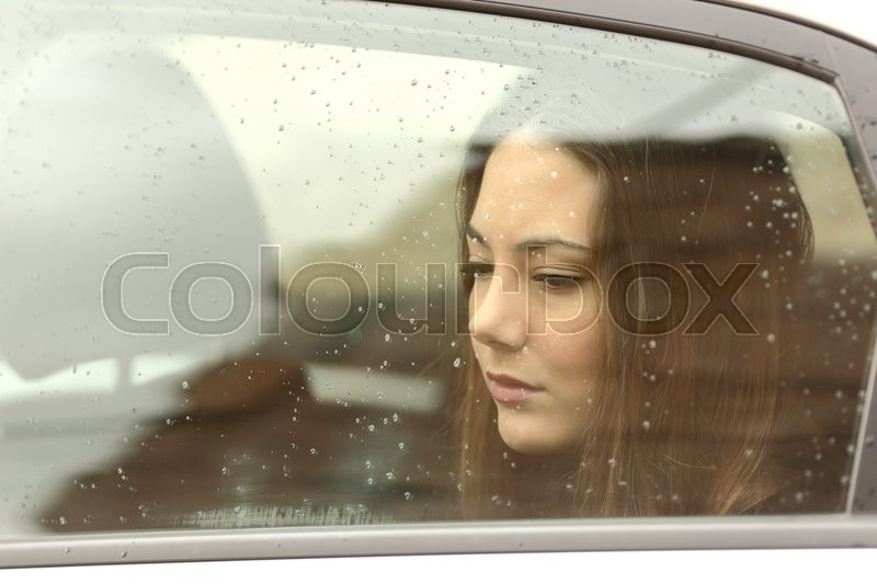 Sad woman looking down through a car window in a rainy day, stock photo