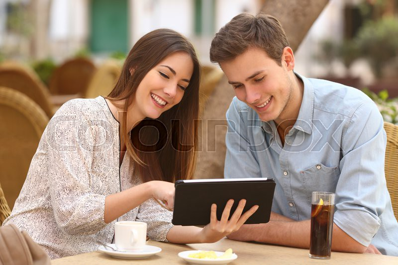 Happy couple watching media in a tablet in a restaurant terrace, stock photo