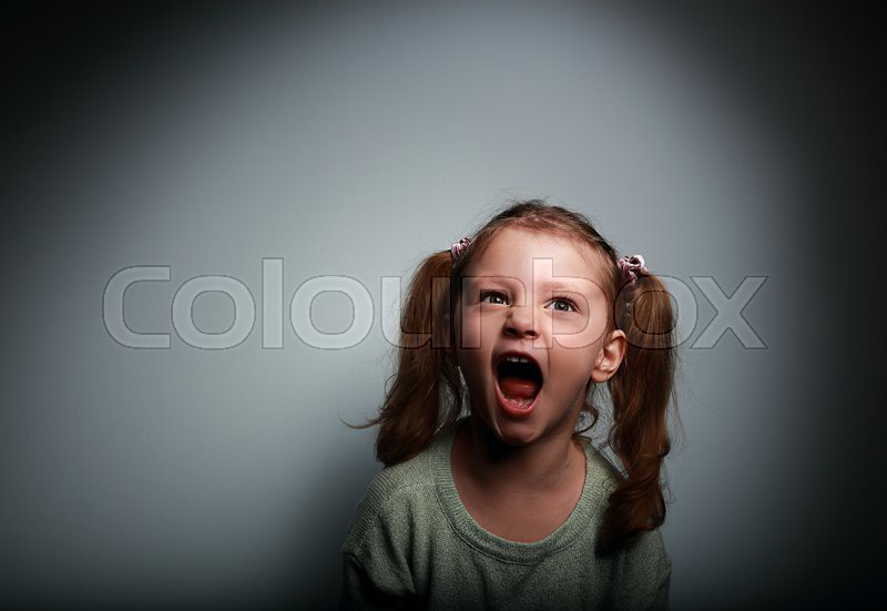 Angry child girl screaming with opened ...