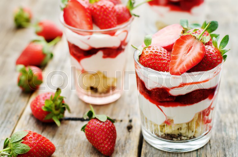Layered dessert with strawberries, biscuit cake and cream cheese on a dark wood background. tinting. selective focus, stock photo