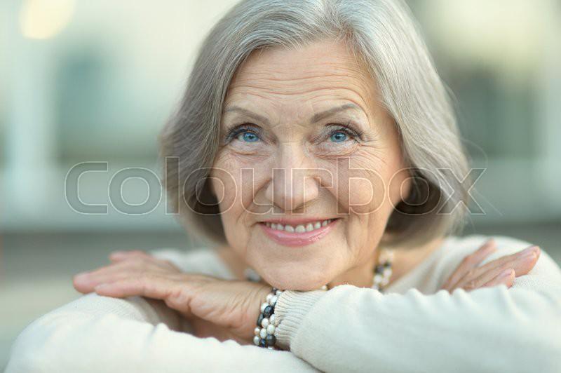 Portrait of a happy Senior woman in autumn park, stock photo