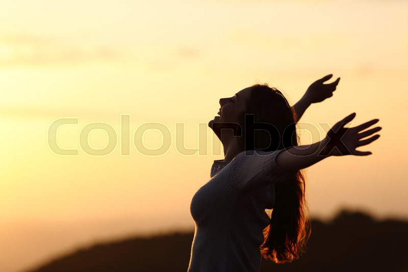 Back light of a woman breathing raising arms with a warm background, stock photo