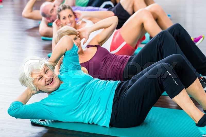 Group of senior people and young woman and men in fitness gym doing sit-ups on the floor, stock photo