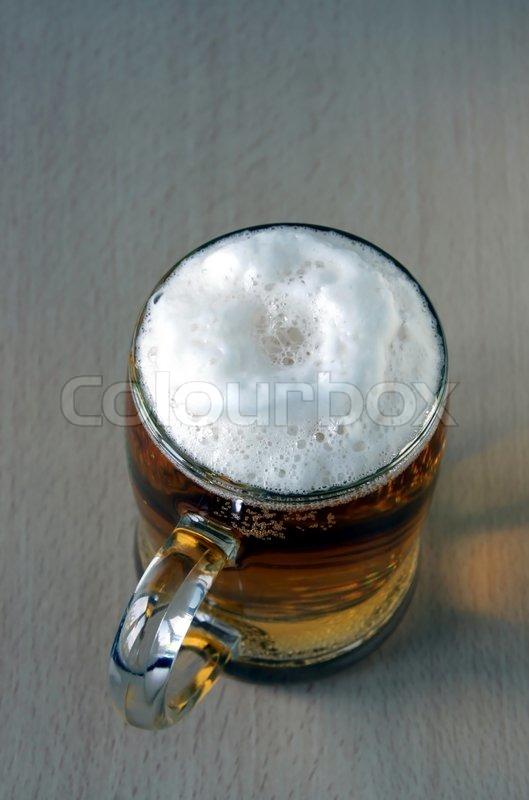 das volle glas mit sch umenden bier kosten auf einem holztisch den obersten punkt der aufnahme. Black Bedroom Furniture Sets. Home Design Ideas