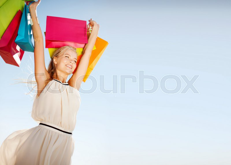 Shopping and tourism concept - woman with shopping bags, stock photo