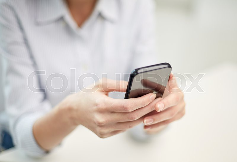 Business, technology and people concept - close up of woman hands texting message on smartphone at office, stock photo
