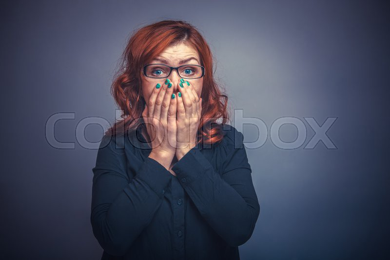 European-looking woman of thirty years covers mouth with her hands, surprised on a gray background retro, stock photo