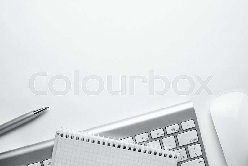 Conceptual White Ballpoint Pen, Clean Spiral Notes, Computer Keyboard and Mouse on Top of White Table with Copy Space at the Center, stock photo