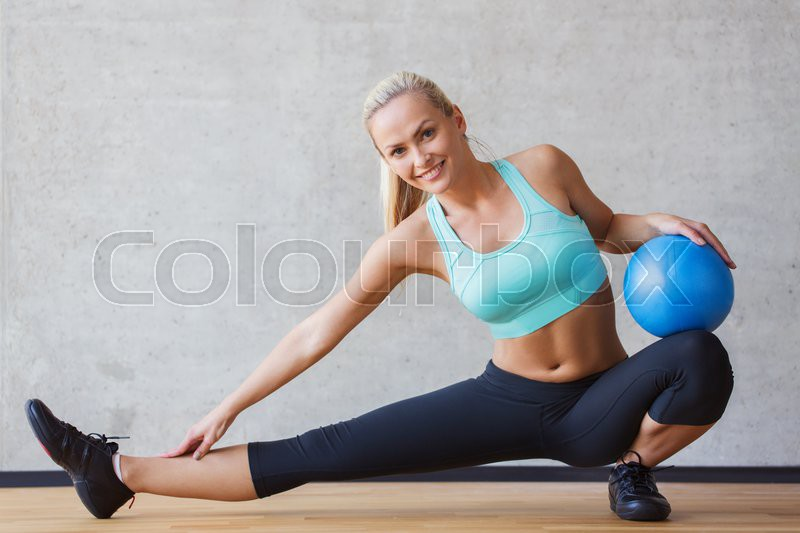 Fitness, sport, training and people concept - smiling woman with exercise ball in gym, stock photo